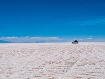 SUV en la sal de Uyuni plana Foto de archivo libre de regalías