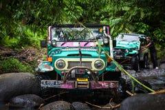 SUV en la selva tropical - aventúrese 7 de marzo de 2013 al entusiasta del coche que vadea un río rocoso usando el coche de cuatr Foto de archivo