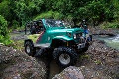 SUV en la selva tropical - aventúrese 7 de marzo de 2013 al entusiasta del coche que vadea un río rocoso usando el coche de cuatr Imagen de archivo