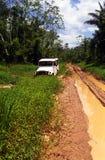 SUV en un rastro fangoso en el bosque del Amazonas foto de archivo