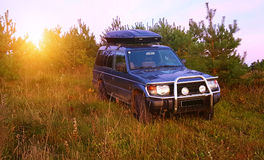 Suv in a field sunset royalty free stock photo