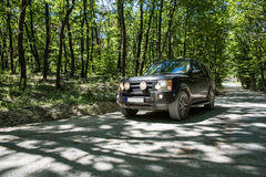 SUV in the forrest. Image showing a black European SUV on a dirt road in the forrest stock photos