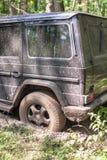 SUV gekregen die in de modder in bos wordt geplakt, off-road Royalty-vrije Stock Afbeelding