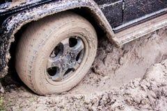 SUV gekregen die in de modder in bos wordt geplakt, off-road Stock Afbeelding