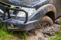 SUV gekregen die in de modder, wielclose-up wordt geplakt Stock Fotografie