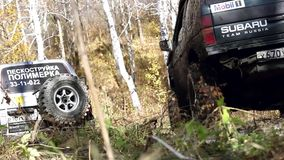 SUV got stuck in the mud and trying to go out in. The autumn forest. HD. 1920x1080 stock video footage