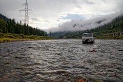 SUV grigio russo attraversa il fiume della montagna con le linee elettriche sulla riva sinistra e su una linea ferroviaria sulla  fotografia stock libera da diritti