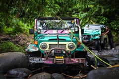 SUV i den tropiska djungeln - för affärsföretagbil för mars som 7, 2013 entusiast vadar en stenig flod genom att använda den ändr Arkivfoto
