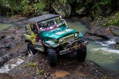 SUV i den tropiska djungeln - för affärsföretagbil för mars som 7, 2013 entusiast vadar en stenig flod genom att använda den ändr Royaltyfri Fotografi