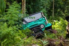 SUV i den tropiska djungeln - för affärsföretagbil för mars som 7, 2013 entusiast vadar en stenig flod genom att använda den ändr Royaltyfri Bild