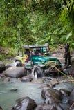 SUV im tropischen Dschungel - wagen Sie 7. März 2013 den Autoenthusiasten, der einen felsigen Fluss unter Verwendung des geändert Stockfotografie