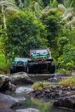 SUV im tropischen Dschungel - wagen Sie 7. März 2013 den Autoenthusiasten, der einen felsigen Fluss unter Verwendung des geändert Stockbilder