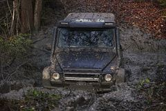 SUV In A Puddle Making Mud Splashes. Royalty Free Stock Photo