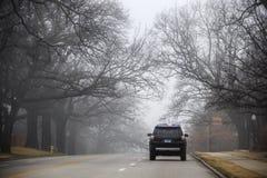 SUV jedzie nad wzgórzem na miasto ulicie pod straszny nagi nadwiesić rozgałęzia się podczas ciężkiej mgły - martwego kona znak fotografia stock