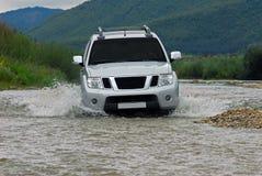 SUV kreuzt den Fluss Lizenzfreie Stockfotografie