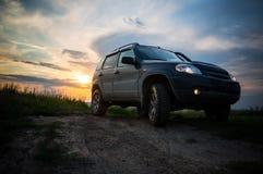 SUV med stora hjul på solnedgången Royaltyfria Bilder