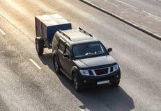 SUV mit Anhänger reitet auf der Autobahn Lizenzfreie Stockbilder