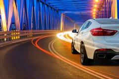 SUV moderno que conduce a través del puente en la noche Imagenes de archivo
