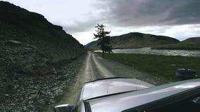 SUV monta en un camino de la alta montaña sobre un río de la montaña Viaje auto: un coche grande mueve adelante el campo De almacen de metraje de vídeo