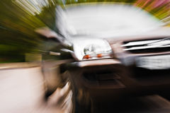 SUV in motion. Closeup of an SUV car in motion on a roadway, driving off-center toward the viewer.  Zoom effect used for power and motion Stock Photos