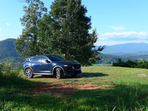 Suv in the mountains with a great view. SUV Car On Off Road In Summer Mountains Landscape. Active Lifestyle, Drive And Travel Concept. SUV on a dirt road in the Royalty Free Stock Images