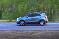 SUV moves on the country road. Blue car moves on the country road Royalty Free Stock Photo
