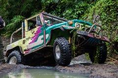 SUV na selva tropical - 7 de março de 2013 entusiasta do carro da aventura que vadeia um rio rochoso usando o carro de quatro rod fotografia de stock royalty free