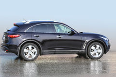 SUV negro en el asfalto mojado Imágenes de archivo libres de regalías