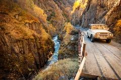 SUV nelle montagne di Caucaso su una strada della montagna Immagini Stock Libere da Diritti