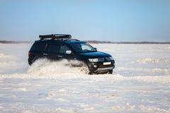 SUV nero che si muove velocemente sulla neve Immagini Stock