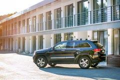 SUV nero parcheggiato su un'area speciale davanti ad una nuova casa urbana su una sera soleggiata di estate all'esterno fotografia stock libera da diritti