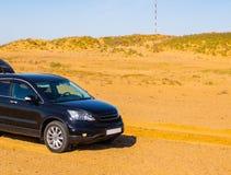 SUV noir dans le désert de sable Déplacement de voiture de concept photographie stock