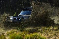 SUV oder Auto nicht für den Straßenverkehr auf dem Weg bedeckt mit Grasüberfahrtpfütze mit Schmutzspritzen Extrem, Herausforderun stockfoto