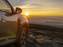 SUV op de bergbovenkant bij zonsopgang stock afbeelding