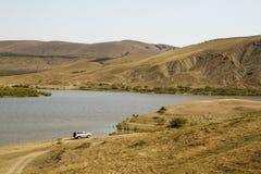 SUV op de kust van het meer tegen de achtergrond van de heuvels stock foto