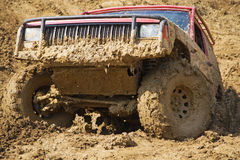 SUV overcomes steep muddy slope. Stock Images
