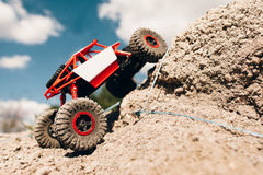 Suv overcoming rock rise, close-up. Rc crawler riding through mountain landscape. Truck overpass offroad rally trace Royalty Free Stock Photos