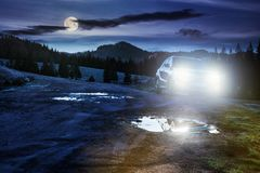 Suv parked on the road near forest at night. Orange suv parked on the country road near forest in mountain at night in full moon light. beautiful autumn scenery royalty free stock photos