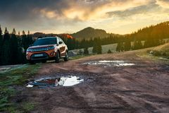 Suv parked on the road near forest at sunrise. Orange suv parked on the country road near forest in mountains at sunrise. beautiful autumn scenery. travel Europe royalty free stock image