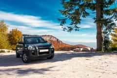 SUV on the parking lot in mountains. Beautiful mountainous scenery with huge rocky formation in the distance. wonderful deep autumn landscape. travel europe by stock photo