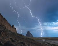 An SUV Races Away from a Thunderstorm at Shiprock, New Mexico Stock Photo