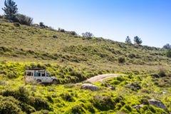 SUV-ritten op de landweg onder heuvels en weiden, Israël Stock Fotografie