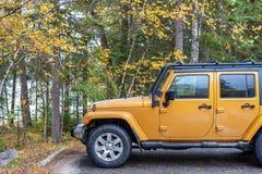 SUV s'est garé à côté du feuillage d'automne et du lac photo libre de droits