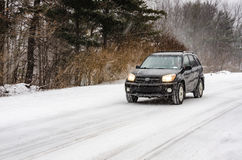 SUV in Snow. Black SUV driving on rural road in heavy snow fall Stock Image
