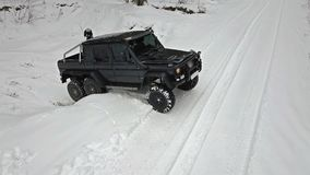 SUV som ska ridas ut ur en djup grop i dentäckte vägen i vinterskogAv-väg lager videofilmer