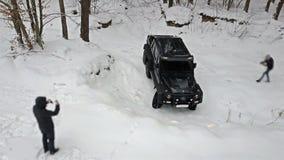 SUV som ska ridas ut ur en djup grop i dentäckte vägen i vinterskogAv-väg arkivfilmer