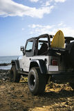 SUV and Surfboard at the Beach Royalty Free Stock Images