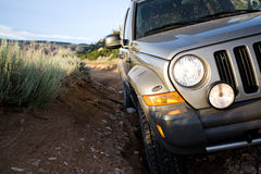 SUV on trail by mountains. SUV 4x4 on a trail at the foot of the mountains Royalty Free Stock Photos