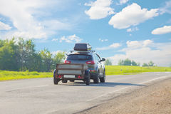 SUV with trailer. Goes on country highway stock photography