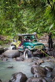 SUV in the tropical jungle - March 7, 2013 Adventure car enthusiast wading a rocky river  using modified four wheel car Stock Photography